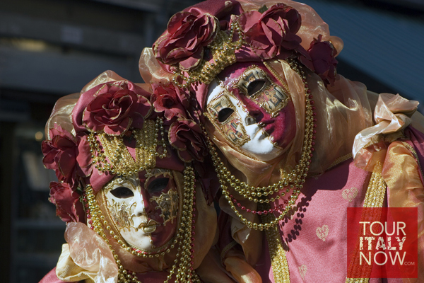 carnevale venice italy - revelers in gold and red masks