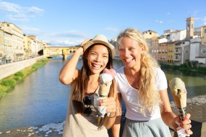 Happy women friends eating ice cream on travel in Florence. Chee