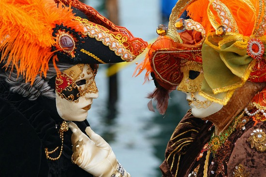 Two masked Venice carnival attendees admire each others' masks.